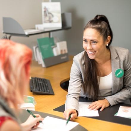 Kuvassa Oma Säästöpankin asiantuntija palvelemassa nuorta naisasiakasta