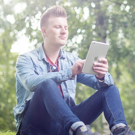 Kuvassa nuorimies puistossa käyttämässä OmaMobiili -sovellusta.
