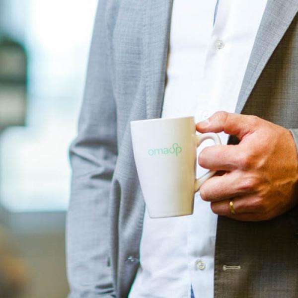 Kuvassa miehen kädessä oleva Oma Säästöpankin kahvikuppi.